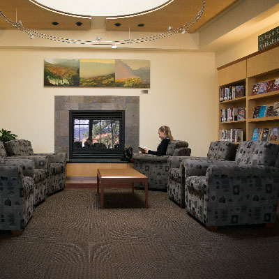 library patron reading in front of fireplace