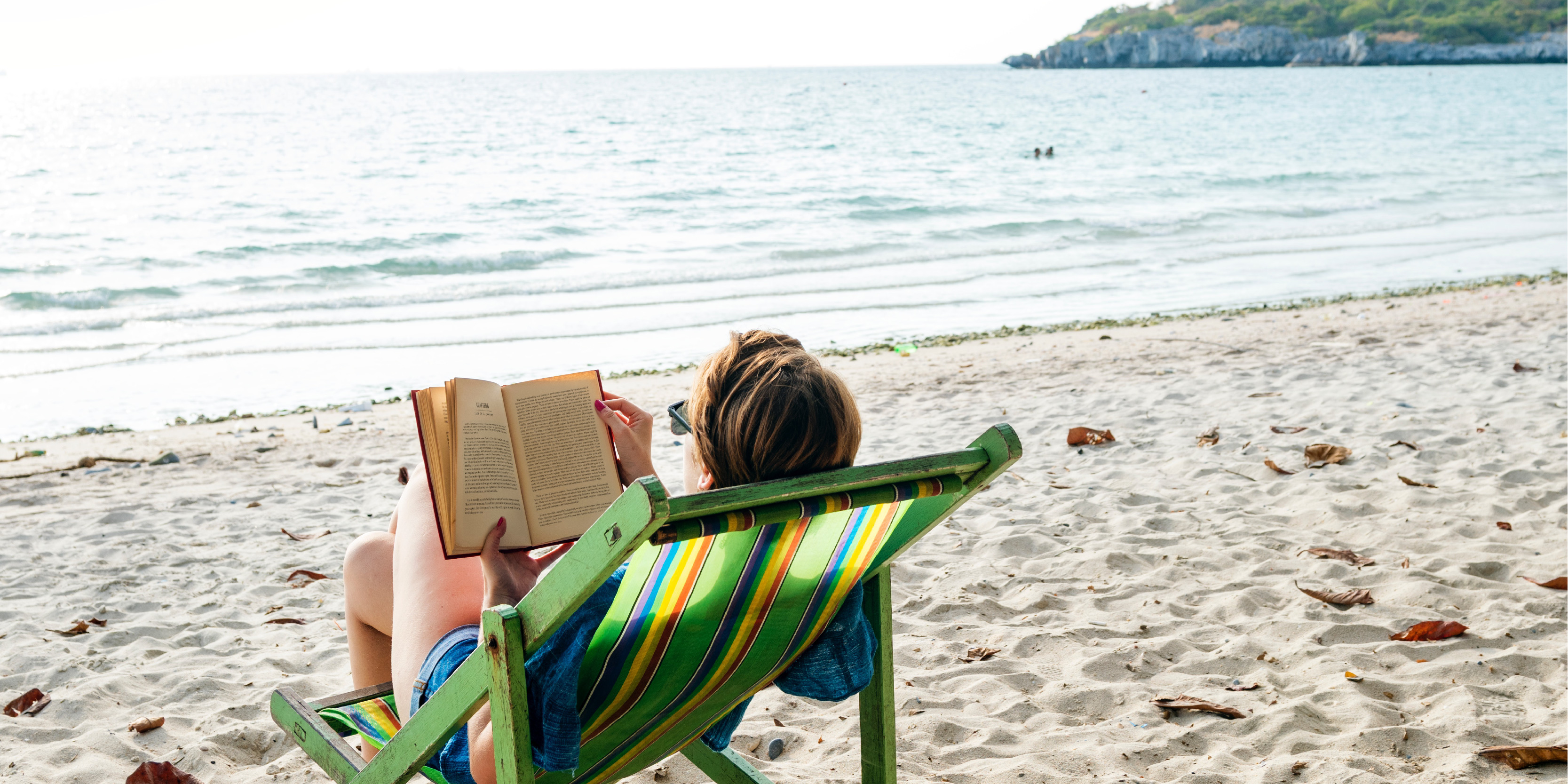 person on a beach reading a book