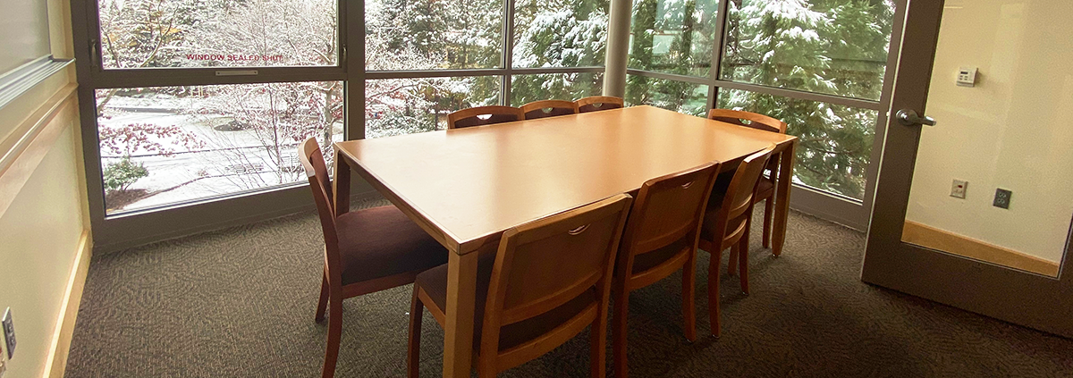 Study room wooden table with six chairs surrounding, windows show snow covered green trees